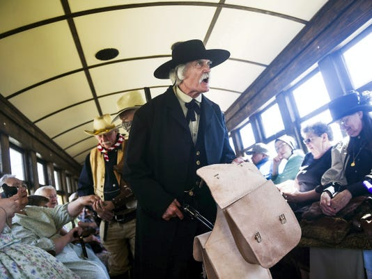 Mike Hall, of Arlington, Virginia, re-enacts a train robbery aboard Steam into History's locomotive ride April 18 during a special train robbery for charity event. Re-enactors portraying members of the James-Younger gang, who were known for their train robberies in Missouri in the 19th century, were 'robbing' passengers for donations for Penn-Mar Human Services, a nonprofit that helps individuals with disabilities.