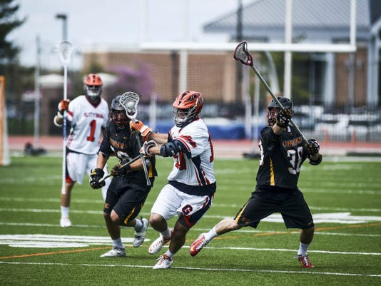 Gettysburg College's Robby Maddux charges past Ursinus defenders Ryan Ridinger, left, and Patrick O'Donoghue, right, during the Centennial Conference championship game Saturday at Gettysburg College.
