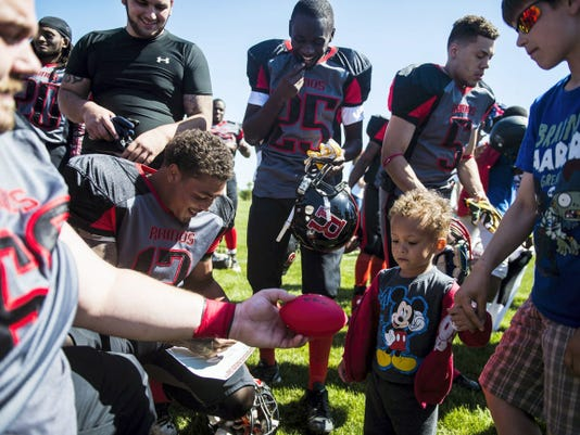 Hanover Rhinos players, from left, Kyle Schriner, Jay Collins, Raymond Henry (25) and Lloyd Welford (5) sign autographs for Jeremiah Myers, 3, of Hanover, and Gabriel Minetos, 10, after the team's game against the Mid-Atlantic Raiders Saturday at Manheim Adventure Park. Hanover won, 32-6, in its last regular season game.