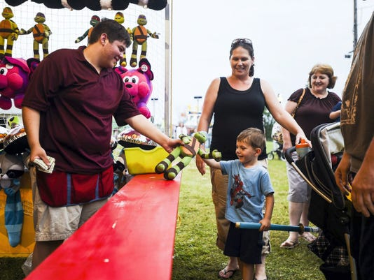 Carnival attendent David Ondeck hands a Teenage Mutant Ninja Turtles doll to Quinn Strausbaugh, 3, of Hanover, while with his parents Andy and Amanda Straausbaugh after his father won at a dart game during the 2014 Gettysburg Fireman's Carnival.