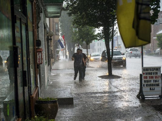 Clare Becker — The Evening Sun Two individuals run for cover on Carlisle Street during the late afternoon downpour on June 1 in Hanover.