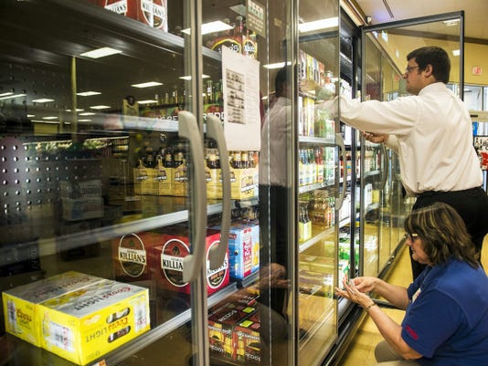 Weis employees Karen Baker and Assistant Manager Adam Mobley stock coolers with beer on Monday.