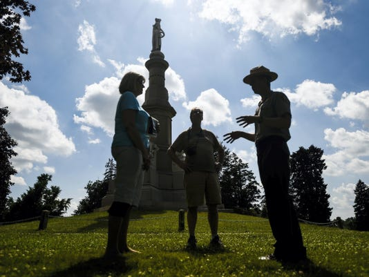 National Park Service Ranger Christopher Gwinn speaks with visitors David and Deborah Ciepluch from Milwaukee, Wis. in 2014 at Soldier's National Cemetery in Gettysburg during one of the free Ranger Programs provided by Gettysburg National Military Park.