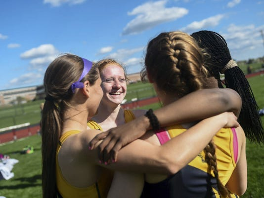 Eastern York's Tia Judy laughs as she strategizes in a huddle with her teammates before the 400-meter relay on Tuesday. The Golden Knights capped their undefeated dual-meet season with a YAIAA Division II championship.