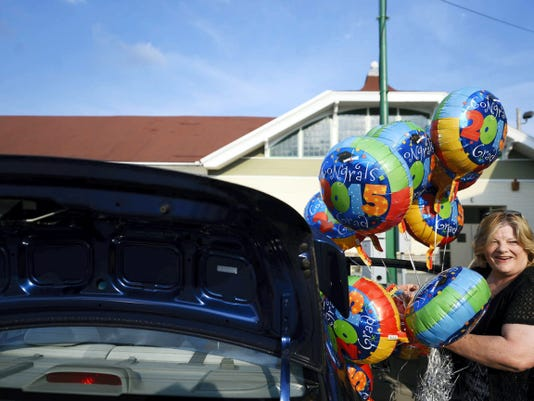 Elaine Long pulls balloons from her car to celebrate the 2015 graduates of Yorktowne Business Institute.