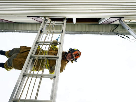 Shiloh firefighter Jessica Fink practices a skill to escape a home being used for training on Loucks Road in West Manchester Township Tuesday, June 30, 2015. Area firefighters have been doing acquired structure training at some houses located on the property of the future Memorial Hospital.