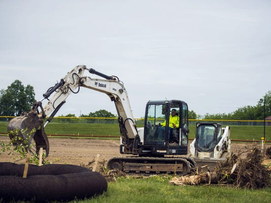 Construction workers move trees May 21 while working on a new soccer, field hockey and softball field at Bermudian Springs School District.