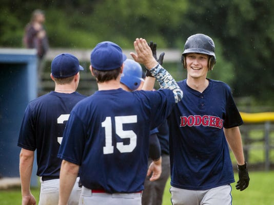 Littlestown Dodgers players head out onto the field to congratulate teammate Sam Wertz for his home run during Thursday's South Penn game against Hanover. Littlestown won, 3-0.