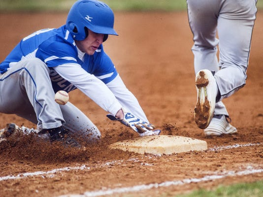 Spring Grove's Trent Baker dives back to first base as South Western misplays the ball.