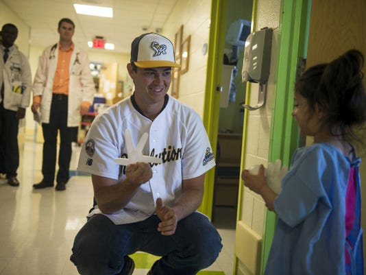 York Revolution pitcher Matt Neil plays with Isabella Surynt, 4, of York, a pediatric patient at WellSpan York Hospital, during a visit by the team Wednesday.