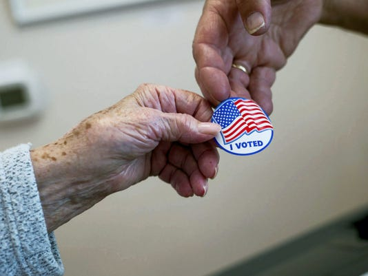 """A poll worker hands a voter an """"I voted"""" sticker on May 20, 2014. Clare Becker - The Evening Sun"""