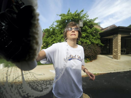 Sue Wise, an employee with the Bon-Ton, cleans windows during a car wash at the Children's Home of York.