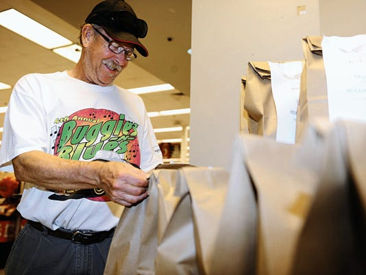 Richard Lubke, a retired Air Force flight engineer, examines a Feds Feed Families food bag in the commissary at Holloman Air Force Base on Aug 18. For less than 10, commissary shoppers, like Lubke, can help feed a local family in need.