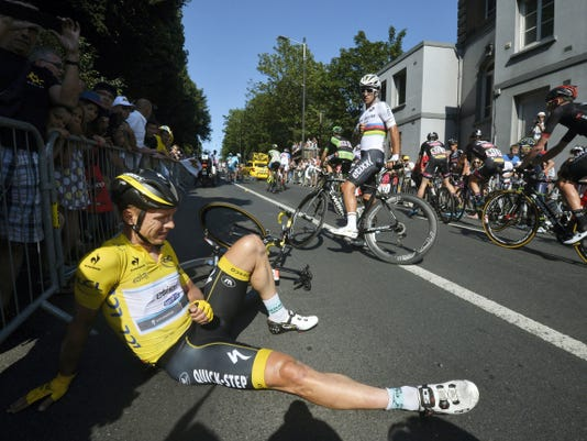 Germany's Tony Martin, wearing the overall leader's yellow jersey, lies on the road with a broken collarbone after crashing in the last kilometers of the sixth stage of the Tour de France in Le Havre, France, Thursday.