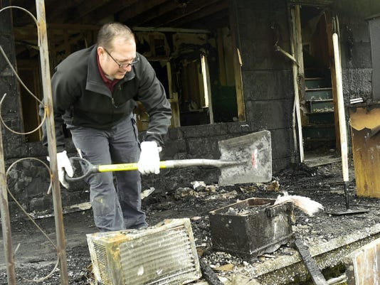 Trooper Frank Hershey, Pennsylvania State Police fire marshal, investigates the cause of a house fire Tuesday morning at 11923 Loop Road, South Mountain.