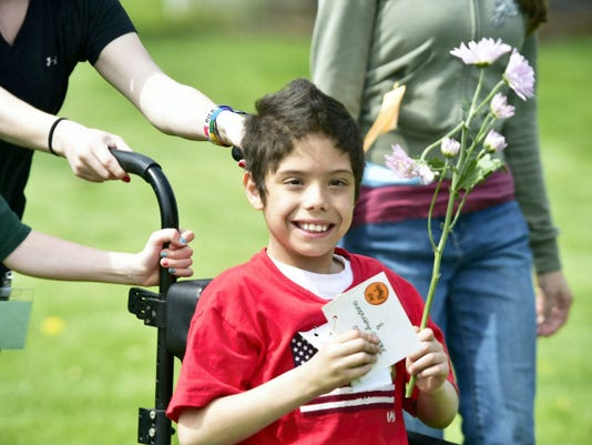 Matthew Ocasio, 9, carries a flower  Thursday, April 30, 2015 during Franklin Learing Center Special Olympics and Field Day.