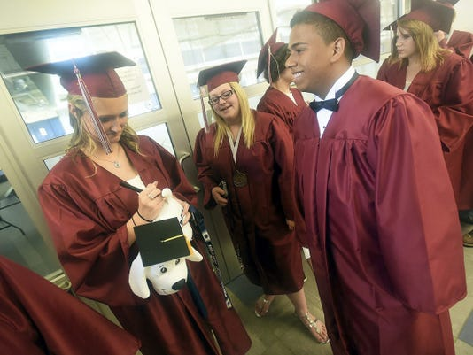 Nicole Baker, left, signs a stuffed dog for Richard Baez before the Shippensburg Area Senior High School Commencement on Wednesday, June 10, 2015. Ryan Blackwell   Public Opinion