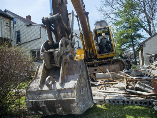 A worker moves debris from the interior of the structure April 13.