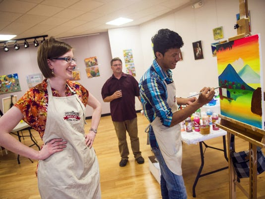 Caitlin Bond, left, of Gettysburg, comments on a painting by Allan Lindo, 19, from León, Nicaragua as he works in the primitivista style of painting May 5 during a class at the Adams County Arts Council.