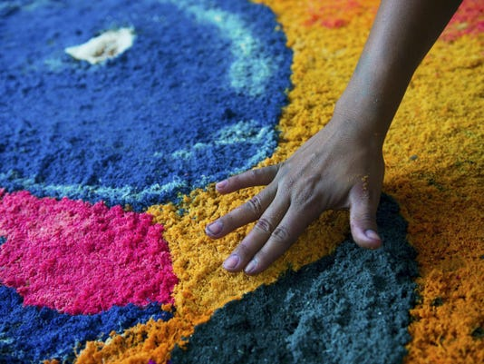 One of the artists smooths sawdust near the eye of a whale depiction May 11. Three Nicaraguan artists designed the carpet, which includes an image of Lincoln Elementary's mascot.