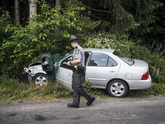 A Pennsylvania State Police trooper examines a vehicle involved in a crash on Brough Road in Berwick Township on June 14.