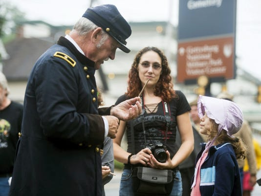 Mike Reetz, of Gettysburg, portraying Brig. Gen. Horace Porter with the reenactor group the Confederation of Union Generals, tells a story to Miranda Brown, 8, from Akron, New York, while her mother, Sabrina Brown, listens at the Rupp House on Baltimore Street in downtown Gettysburg on Saturday. Early rain and some postponements kept heavy crowds away on Saturday