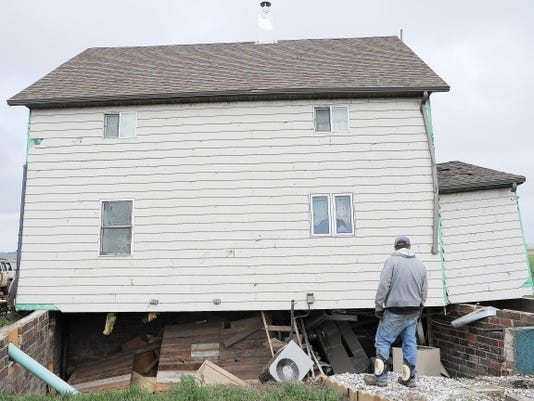 James Fink looks down into the basement of family friend Mike Fechner's home after it was moved off its foundation by a tornado on Sunday, May 10, 2015, near Delmont, S.D. The tornado hit the town southwest of Sioux Falls on Sunday morning, injuring nine people and damaging at least 20 buildings, including a century-old church. Two people remain hospitalized. Crews are working to restore water, electricity and phone service. (Joe Ahlquist/The Argus Leader via AP) NO SALES