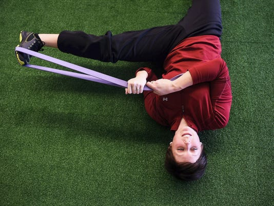 Ashley Peck, of Glenville, stretches during a physical training session with her husband, Todd, who's a professional NASCAR driver, April 10 at Elite Performance Sports in New Oxford. The physical training center recently moved locations from Spring Grove to New Oxford on Carlisle Pike.