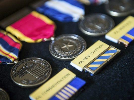 Arthur Cunningham keeps a box of his pilot awards.