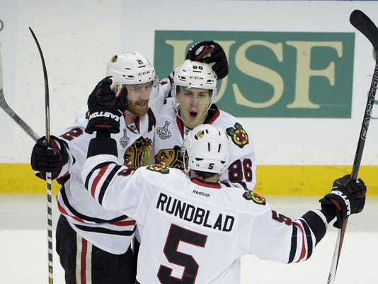 Chicago Blackhawks left wing Teuvo Teravainen, top right, celebrates his goal with Duncan Keith, left, and David Rundblad during the third period on Wednesday in Game 1 of the Stanley Cup Final against the Tampa Bay Lightning. The Blackhawks won 2-1.