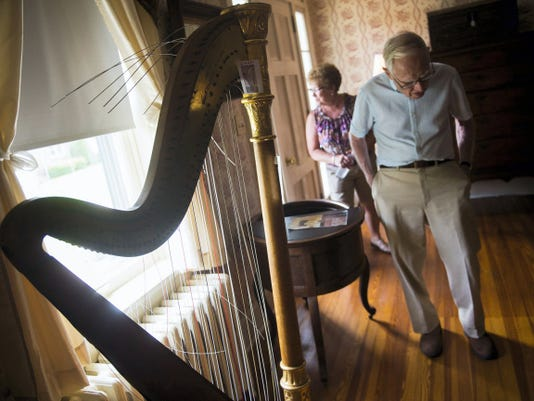 C. Robert Martin, of Hanover, looks over items set for auction in Marion Thomas Harbaugh's living room during an auction preview Sunday. The concert harp and hundreds of other items from Harbaugh's estate will be for sale Friday and Saturday.