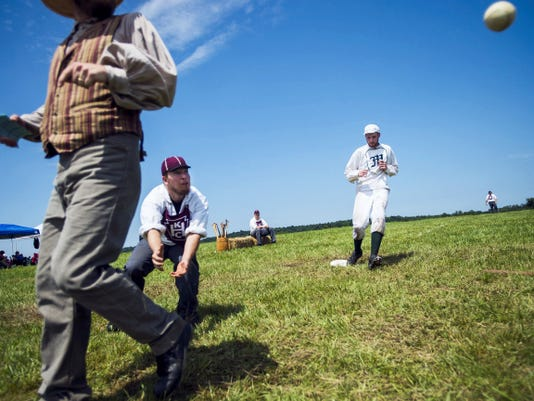 A runner rounds third for home plate as The Keystone Base Ball Club of Harrisburg takes on the Mutual Base Ball Club of New York Saturday during the Gettysburg National 19th Century Base Ball Festival at Schroeder Farm.