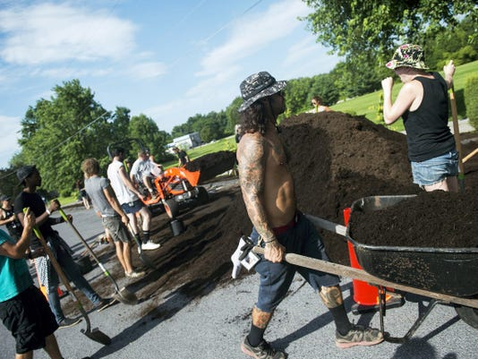 Volunteers from the 2015 Vans Warped Tour work to distribute a pile of mulch around the newly planted trees on Monday.