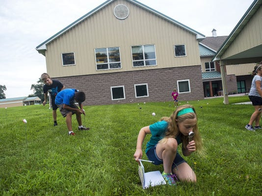 Malina Reber tests out a cottonball scented with different fragrances during an exercise designed to teach students about pheromones at the 4-H Ag Explorers Day Camp in Gettysburg on July 21, 2015.