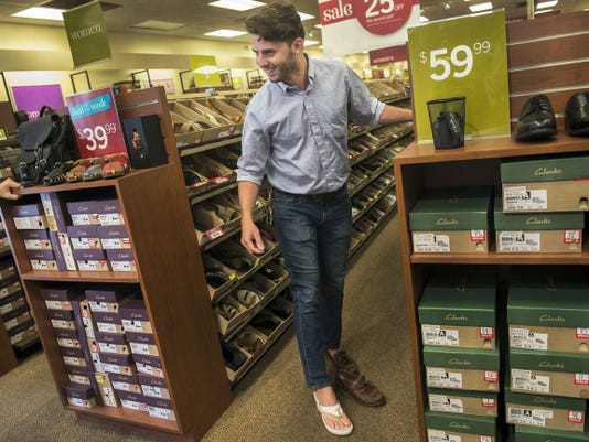 Clarks employee Adam Grove tries on a shoe to the amusement of his co-workers on Aug. 2. Grove said he would like to participate in the event for a good cause.
