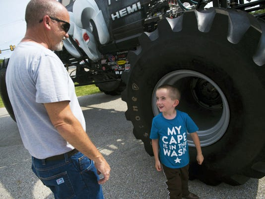 Adam Lawrence, 5, reacts to the size of the Raminator's tires while visiting the truck with his dad, Ted Lawrence, both of McSherrystown, at Hanover's Apple Chrysler Dodge Jeep Ram on Monday.