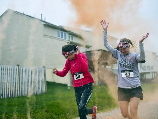 Runners get a splash of colored corn starch April 25 during the Hanover YWCA's first 5K Color Run for Race Against Racism at Moul Field in Hanover.