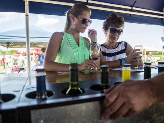 Kylie Hakes, of East Berlin, left, samples wine varieties with her soon-to-be mother-in-law, Sue Noble, of New Oxford, at the Jackson Square Vineyard tent at Wine Tasting in the Hamptons on Sunday. The women said they were celebrating two life events: Hakes heading to Pittsburgh for graduate school and Noble's new grandbaby.