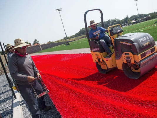 Crews lay out turf on Bermudian Spring School District's multipurpose field Monday despite hot temperatures.