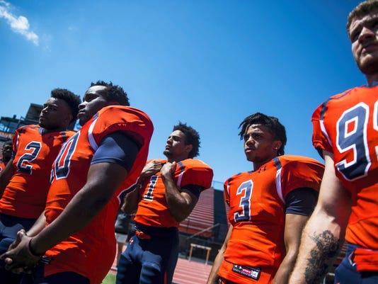 Players listen to instructions for photo shoots during media day at Gettysburg College on Saturday.
