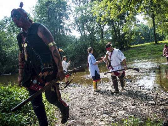 Re-enactors portraying Native Americans with the Shawnee tribe, Tom Hinkelman, of Mount Laurel, New Jersey, left, and Eric Beachy, of Chambersburg, middle, pick up some watermelon from re-enactor Elizabeth Huxford while crossing the creek after participating in a re-enactment of a skirmish between British and French and Shawnee forces during Mason and Dixon Day at the Mary-Penn Bed and Breakfast on Saturday Aug. 29 near Gettysburg. The event, celebrating the history of the surveying of the Mason and Dixon line and the French and Indian War, also known as the Seven Years War, is a first time event for Adams County.