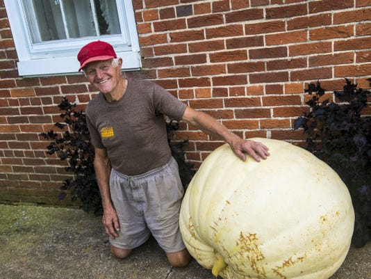 Hanover area farmer Ben Klunk poses next to the Atlantic Giant pumpkin weighing 325 pounds, 4 ounces, on Aug. 31.