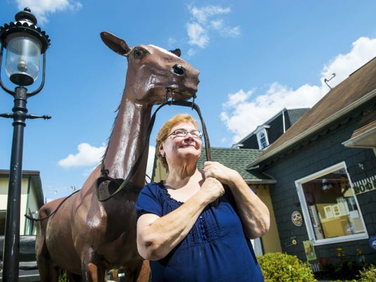 "Bernadette Loefell-Atkins, owner of Gettysburg Battlefield Books & Collectibles, poses with Old Ned, a fiberglass horse that has been a part of the Old Gettysburg Village shopping center since 1963. Loefell-Atkins is currently planning to undergo restoration of the horse to ensure he remains a landmark of the Old Gettysburg Village. ""There's been a real outcry to save him so I am going to do it,"" said Loefell-Atkins. ""I know I can do it."""
