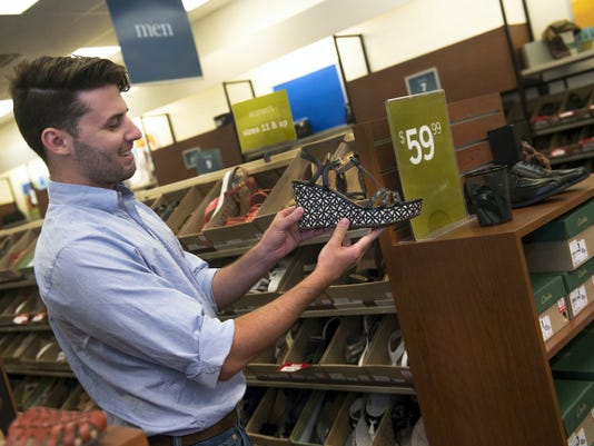 Clarks sales employee Adam Grove shows some examples of the shoes they have in stock that may be of interest for the Walk a Mile in Her Shoes event on Aug. 14.