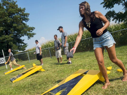 Andrea Newberry, of Abbottstown, pitches a bean bag during a game of corn hole despite the blazing sun Sunday.
