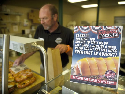 Al Nelson puts together a pretzel order for a customer Tuesday afternoon. The Philly Pretzel Factory will give away 500 pretzel-wrapped hot dogs on Thursday to celebrate National Hot Dog Day.