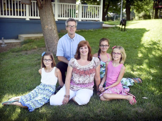 """Cancer survivor Tina Horengic poses with her daughters, from left, Rachel, 11, Hannah, 12, and Grace, 9, and husband, Mike, in the front yard of their Lebanon County home. Horengic will participate in the upcoming """"Conquer Cancer with a Quarter"""" event next week at the Lebanon Valley Mall."""