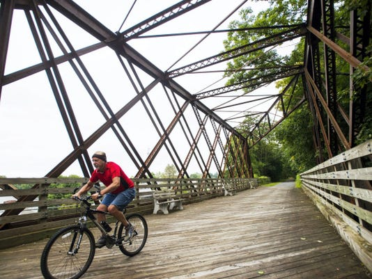 A man rides his bike over the historic iron bridge on the Lebanon Valley Rail Trail in Cornwall on Monday. Despite a dreary day, hikers and bikers were still out and about on the trail.