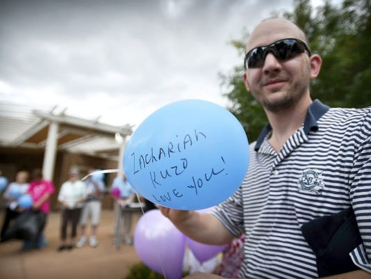Nathan Kuzo, brother of Zachariah Kuzo, writes a simple message on a balloon before releasing it Thursday afternoon at Spang Crest Manor in Lebanon. Zachariah, who worked at the nursing home, died Aug. 16 of cancer.