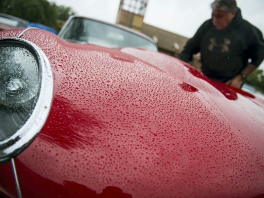 "Harold Zabady wipes off his 1964 Jaguar E Type. Despite the rain Saturday, The Knights of Columbus Council 9875 held its first ""Cruise for a Knight"" car show at St. Paul the Apostle Church in Annville to benefit local charities."